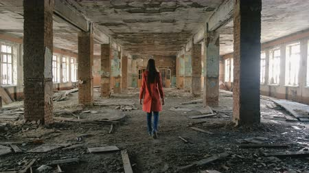 наводнение : Unrecognizable woman in a red cloak inspects destroyed building after the disaster earthquake, flood, fire.