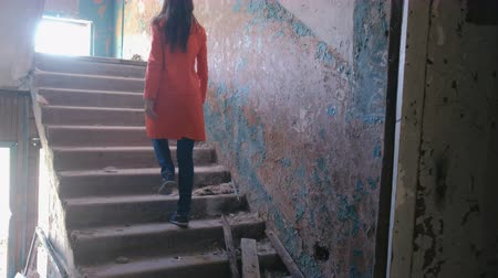 aftermath : Woman in a red cloak inspects destroyed building after the disaster earthquake, flood, fire. Go up the stairs.