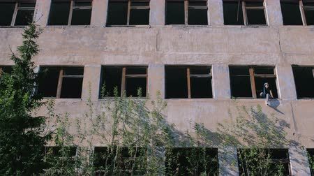 zbourán : Woman sitting on window of destroyed multi-storey building with many broken windows. Dostupné videozáznamy