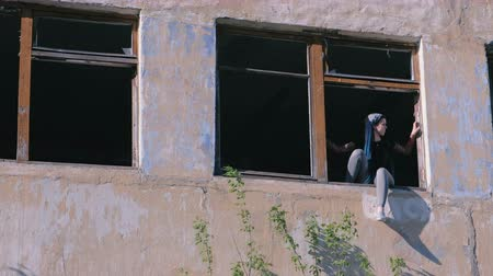 csattanás : Woman sitting on window of destroyed multi-storey building with many broken windows. Stock mozgókép