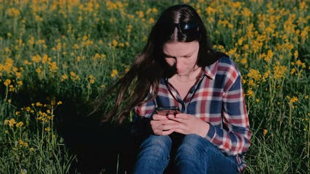 reen : Woman looking at mobile phone sitting in Park on grass among yellow flowers.