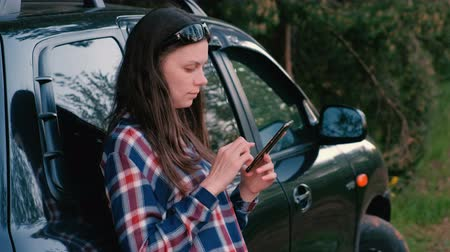 pojištění : Woman sends a message on the phone standing next to the car.