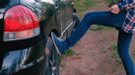 reporting : Woman kicks the wheel of the car. Waits for help. Stock Footage