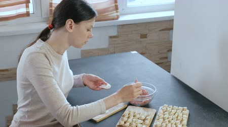 pelmeni : Woman makes dumplings with mince meat. Side view. Stock Footage