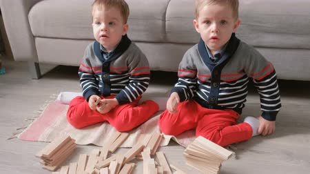 dvojčata : Twins boys brothers are building from wooden blocks sitting on the floor by the sofa in their room.