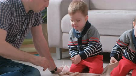 образовательный : Family mom, dad and two twin brothers play together building out of wooden blocks on the floor.