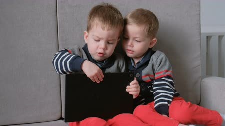 náklonnost : Two twin brothers toddlers playing together games on tablet sitting on the sofa.