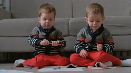 small pen : Two twin brothers toddlers draw together markers sitting on the floor.