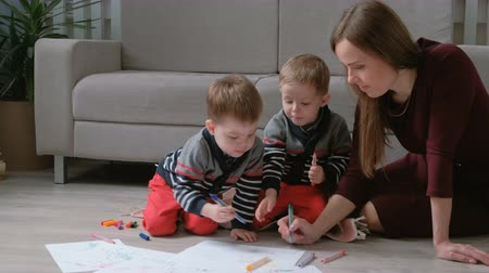 marker pen : Family mom and two twin brothers draw together markers and felt pens sitting on the floor. Stock Footage