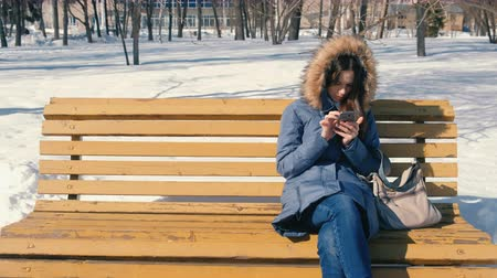 wooden type : Woman types a message on her phone sitting on the bench in winter city park in sunny day.