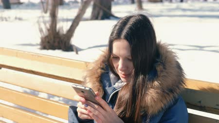 wooden type : Happy young woman brunette types a message on her phone sitting on the bench in winter city park in sunny day.
