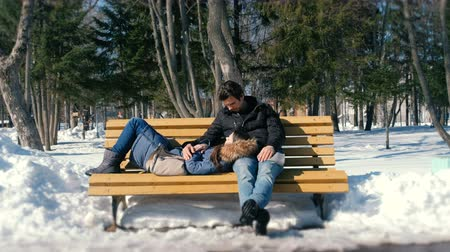 snow caps : Man and a woman rest together on a bench in the winter city Park. Sunny winter day. Stock Footage