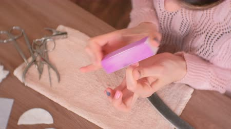 püskül : Woman polishes her nails with buff and nail file before remove shellac. Close-up hands.