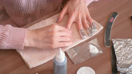 toalha : Removing gel Polish from nails. Woman pours remove liquid on a cotton pad, puts it on a nail and wraps the foil. Close-up hands.