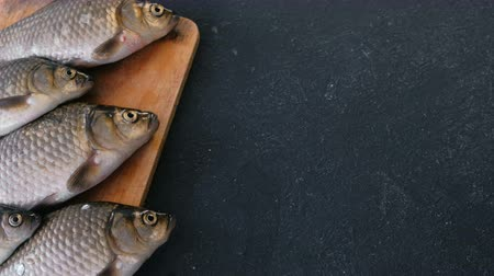 для продажи : Cooking fish. Fresh small carps on the table on a wooden Board close-up. Стоковые видеозаписи