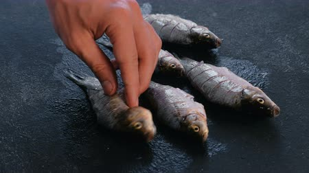 turn table : Man turns the carps fish on the table and sprinkles it with spices. Cooking fish. Hand close-up.