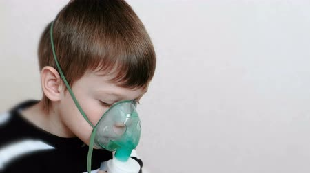 sedative : Use nebulizer and inhaler for the treatment. Boy inhaling through inhaler mask. Side view.