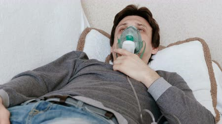 sedative : Use nebulizer and inhaler for the treatment. Young man inhaling through inhaler mask lying on the couch. Front view.