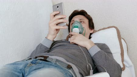 respiratory infection : Use nebulizer and inhaler for the treatment. Young woman inhaling through inhaler mask lying on the couch and chatting in mobile phone. Side view.
