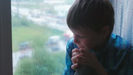 crying baby : Crying boy looks out the window in the rain and is sad.