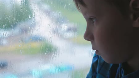 fall through : Boy looks out the window in the rain and is sad.