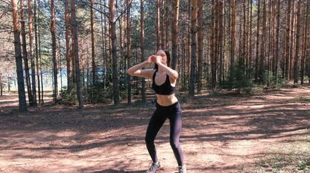 letecký : Woman doing sports exercises in the woods by the lake. Slow motion.