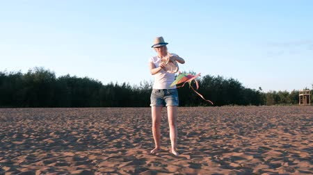 коршун : Beautiful blonde in a hat launches a kite on the beach.