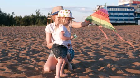 коршун : Beautiful blonde in a hat mom and daughter launches a kite on the beach. Стоковые видеозаписи