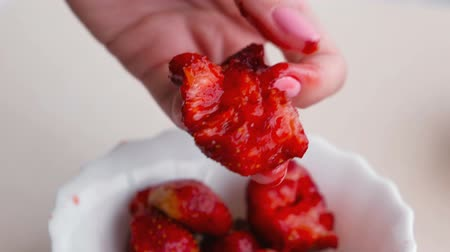 frutoso : Woman kneads strawberry in her hand making jam.