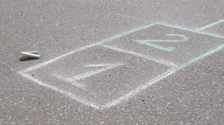 recess : Hopscotch on asphalt with chalks.