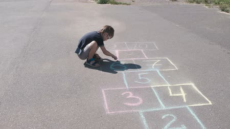 sandalet : Boy is drawing hopscotch on the asphalt. Stok Video