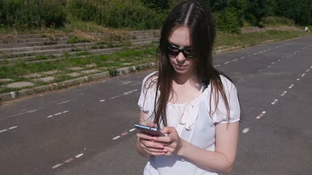 schoolyard : Young brunette girl walking in the stadium and typing a message on a mobile phone and smiling. Stock Footage