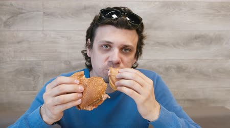 baton : Man eating a hamburger and shawarma simultaneously sitting in cafe.