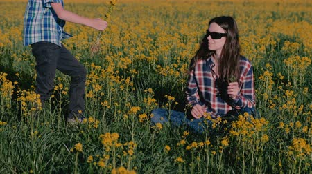 dávat : Boy gives his mother a bouquet of wild flowers and kisses her sitting on the grass among the yellow flowers. Dostupné videozáznamy