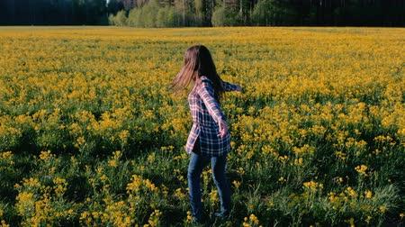 prairie : Brunette woman is spinning in the middle of a field with yellow flowers.