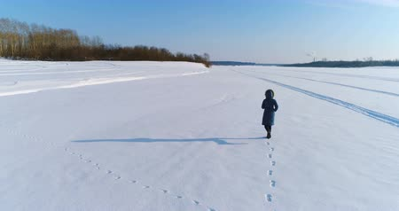 ślady stóp : Aerial footage of running woman in winter landscape of a frozen river with a forest and a view of the city with factories. Back view.