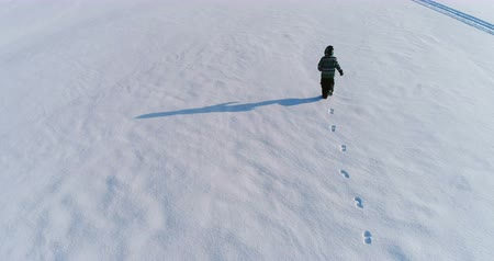 flee : Boy is running on a snow covered area, laying on the snow and makes snow angel, aerial footage.