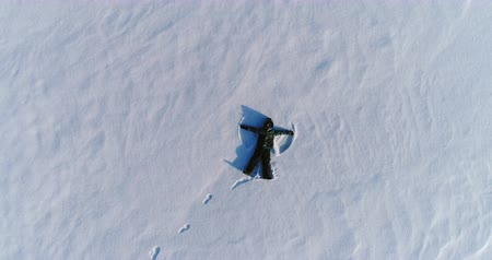ślady stóp : Boy of 7 years in blue jacket makes snow angel, aerial footage. Camera slowly is rising Wideo