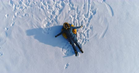 pegada : Woman is laying on tubing in the snow. Camera slowly rising. Aerial footage.