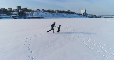 flee : Mom and sun is running and playing together in snow. Aerial footage. Family pastime in winter.