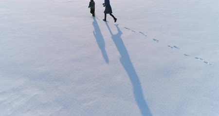 flee : Mom and sun are running together in snow. Aerial footage. Family pastime in winter. Stock Footage