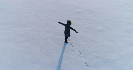 flee : Woman is spinning in snow covered area in winter, aerial video.