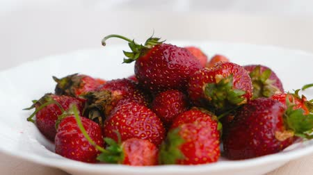 fruity garden : Juicy appetizing tasty strawberry on a white plate. Close-up. Stock Footage