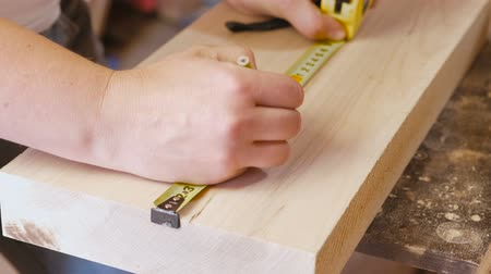 housing problems : Worker measures the tape measure and pencil distance on the wood Board. Joinery. Hands close-up. Stock Footage