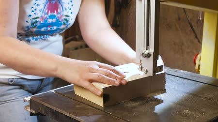 bandsaw : Craftswoman is cutting a wood toy cars workpiece from wood with bandsaw. Hands close-up.