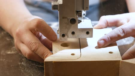 craftswoman : Craftswoman is cutting a wood workpiece from wood with bandsaw. Close-up hands.