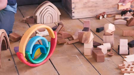 usado : Children are playing with wooden toys. Close-up hands.