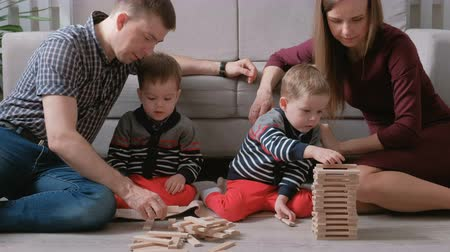 dvojčata : Family mom, dad and two twin brothers play together building out of wooden blocks on the floor.