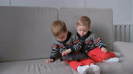 dvojčata : Two twin brothers take away each others tablet sitting on the sofa. Kids play games on the tablet.