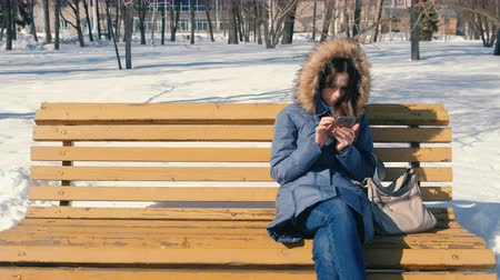 pelz kapuze : Woman is browsing internet on her phone sitting on the bench in winter city park in sunny day. Videos